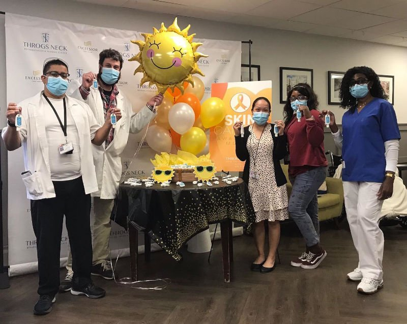 Group of employees standing around a table with sunshine balloon
